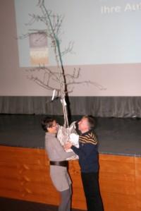 Eva Prantl überreicht dem Präsidenten Martin Trafoier von Polar Bear Society Vinschgau einen hochstämmigen Palabirn-Baum